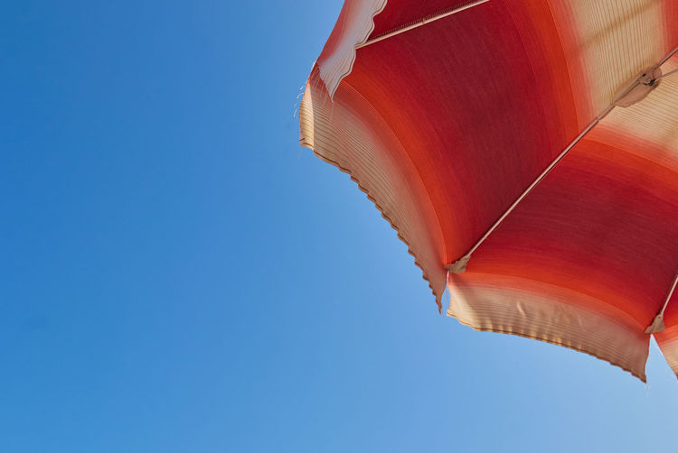Beach Umbrella Blue Clear Sky Copy Space Day Human Body Part Low Angle View Nature One Person Outdoors Parasol Protection Red Security Shade Sky Umbrella Unrecognizable Person Wind