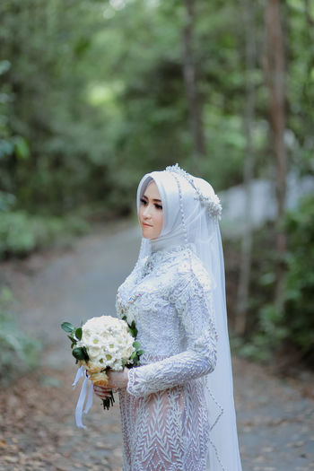 Bride wearing traditional clothing standing in forest