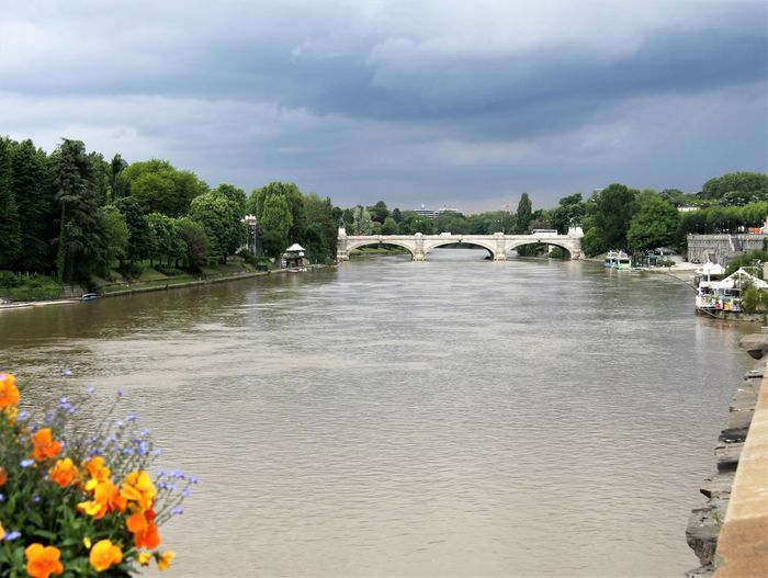Scenic view of river by bridge against sky
