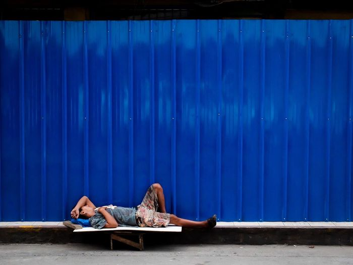Side view of beggar sleeping against blue metallic wall