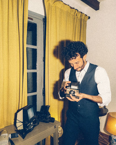 Full length of man photographing with polaroid camera