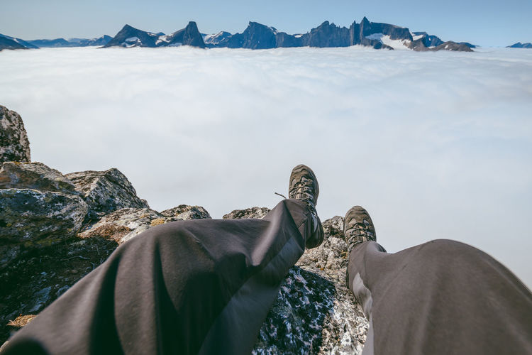Low section of man sitting on mountain with clouds in background