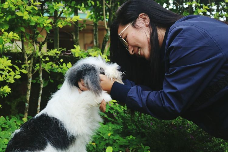 Side view of young woman holding dog against plants