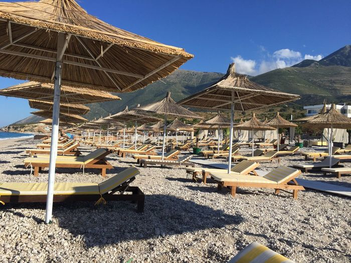 Lounge chairs and thatched roofs against sky