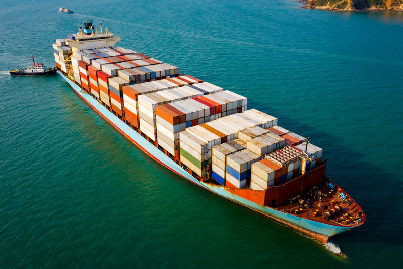 Aerial view large container ship and tug boat for logistics, import export, or transportation
