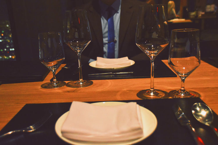 Midsection of man wearing suit while sitting at dining table in restaurant
