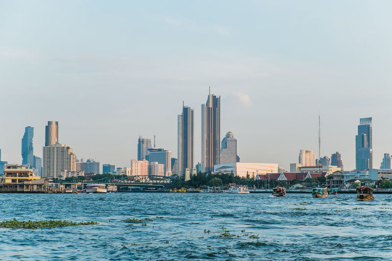 Landscape view of buildings at the chao phraya riverside and boats in the river.
