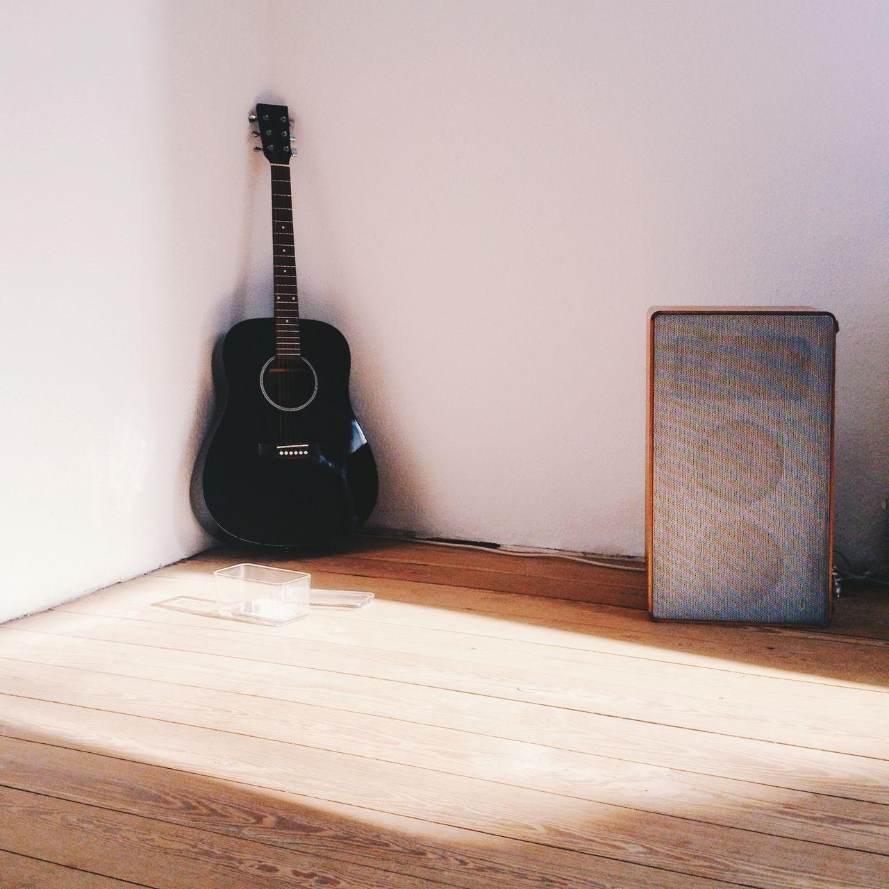 Guitar and speaker on hardwood floor
