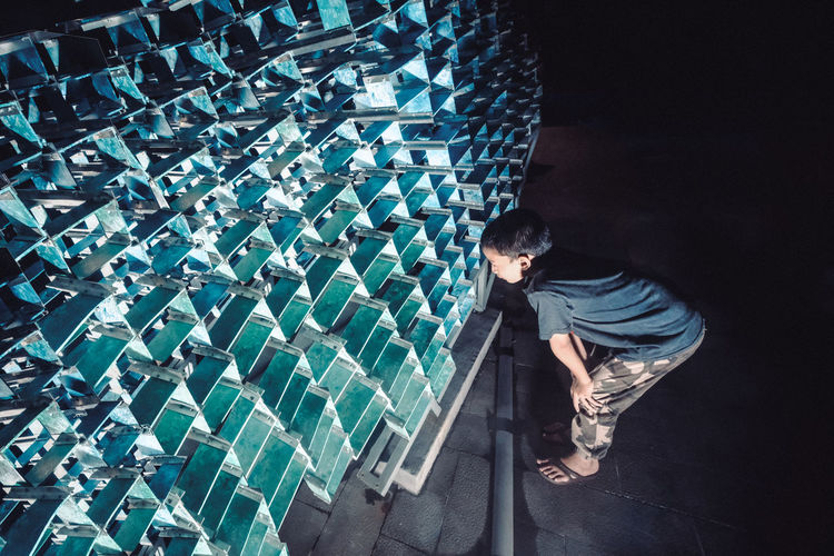 Boy looking at metallic structure during night