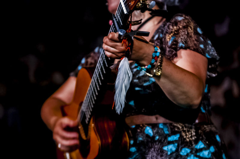 Midsection of female musician playing guitar during concert