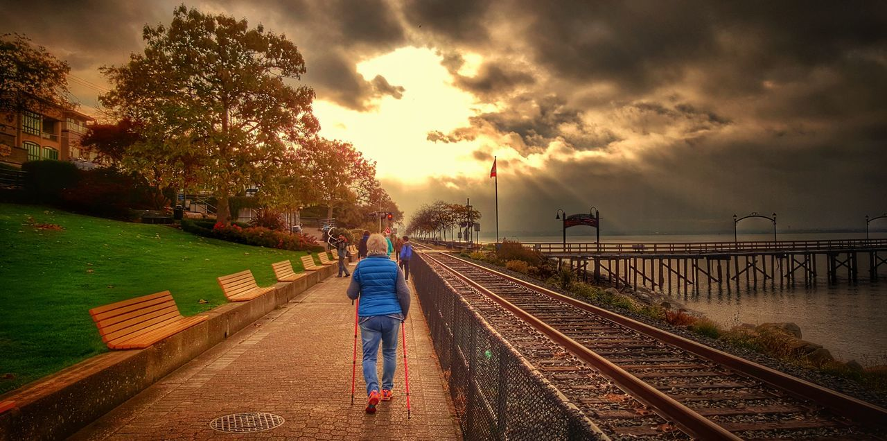 full length, rear view, real people, walking, sunset, sky, cloud - sky, bridge - man made structure, women, railroad track, transportation, outdoors, built structure, the way forward, lifestyles, leisure activity, water, one person, nature, men, tree, architecture, footbridge, day, beauty in nature, adult, people