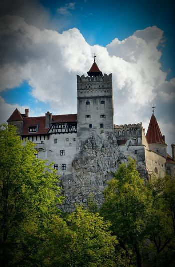 Low Angle View Of Trees And Bran Castle Against Cloudy Sky
