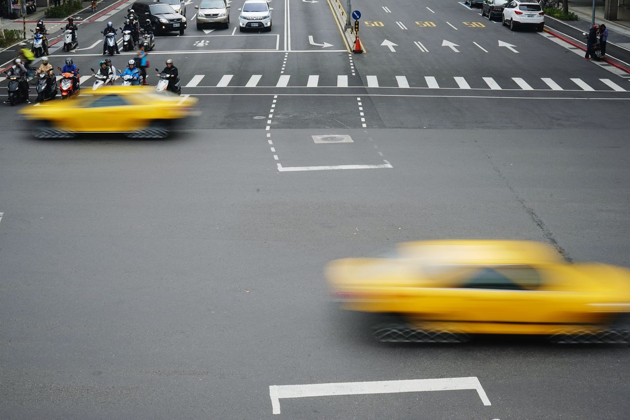 Blurred Motion Of Taxis Moving On Road In City