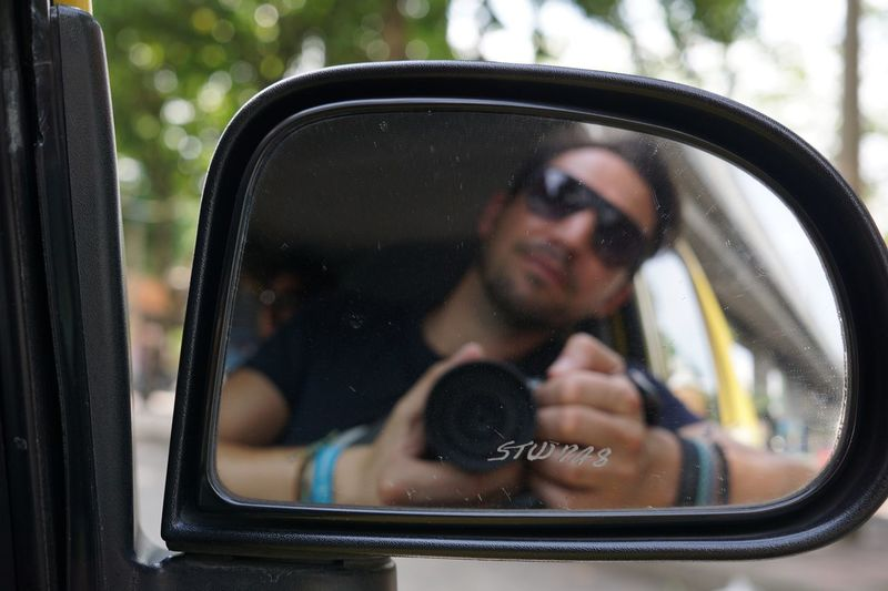 Portrait of man photographing through camera
