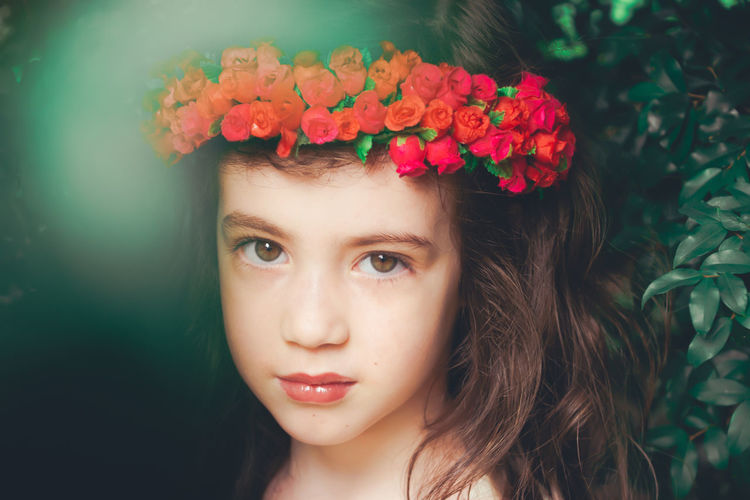 Close-Up Portrait Of Cute Girl Wearing Red Flowers