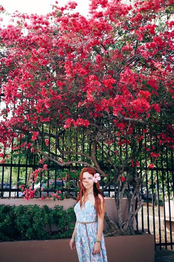 Young woman standing against red tree