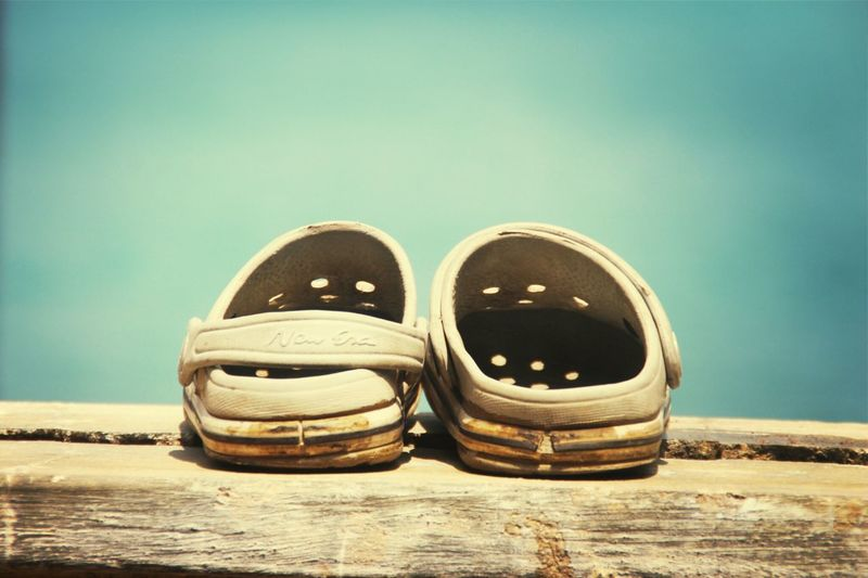 Close-up of shoes on table against blue background