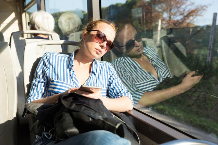 Mid adult woman wearing sunglasses sleeping at bus