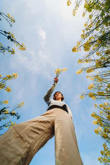 Low angle view of woman against sky with flowers