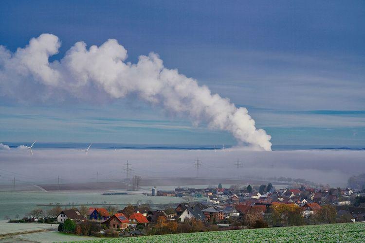 Smoke emitting from chimney on landscape against sky