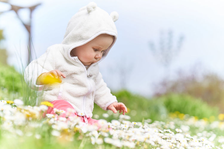 Child Flower Childhood Flowering Plant Plant One Person Baby Young Innocence Real People Beauty In Nature Day Nature Three Quarter Length Freshness Selective Focus Cute Babyhood Warm Clothing Outdoors