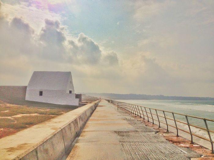 Narrow pathway along calm sea
