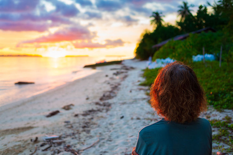 Rear view of woman looking at beach during sunset