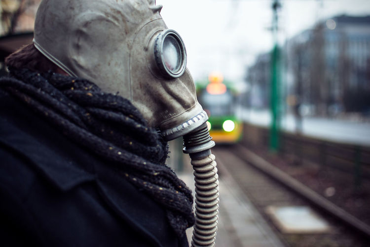 Side view of man wearing gas mask while standing at railroad station platform