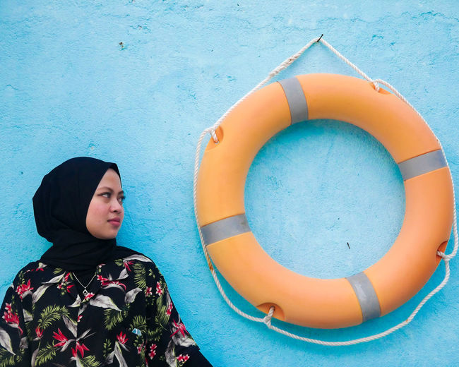 Young woman wearing hijab looking at life belt hanging on blue wall