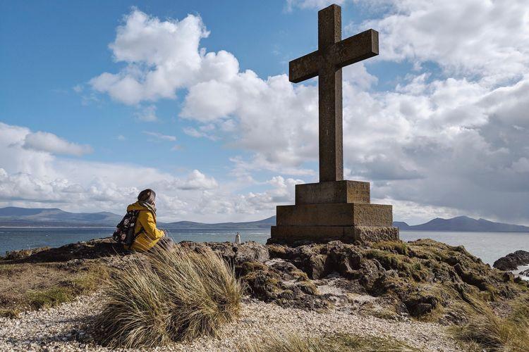 Cross on rock by sea against sky