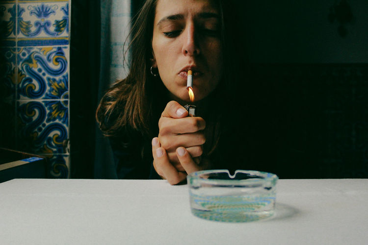 Young Woman Lighting Cigarette At Table