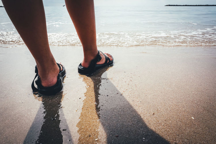 Summer Vacation and Travel Concept. Close Up of Female Legs Stand on Beach Human Leg Low Section Human Body Part Body Part Water Beach Sea Shoe Real People One Person Day Land Nature Lifestyles Leisure Activity Sunlight Standing Motion Outdoors Human Foot Human Limb