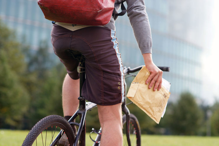 Midsection Of Man Riding Bicycle In City