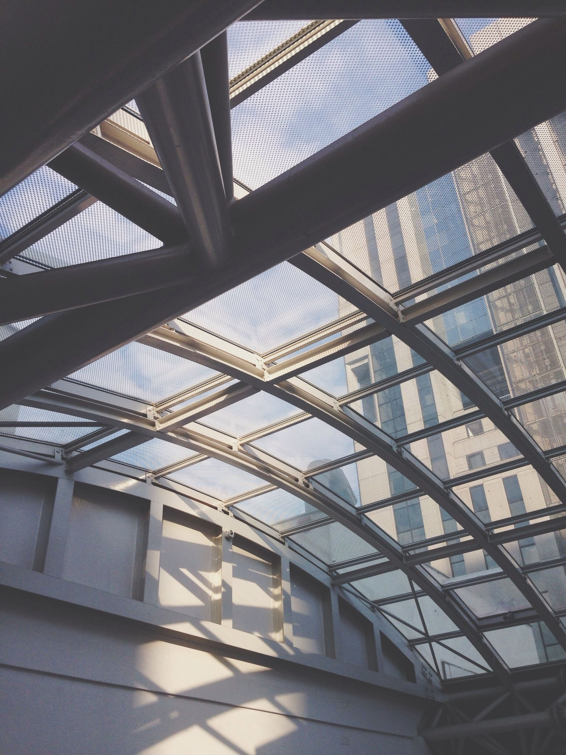 architecture, built structure, low angle view, indoors, modern, building exterior, glass - material, building, ceiling, pattern, architectural feature, window, directly below, day, office building, no people, sky, city, railing, skylight