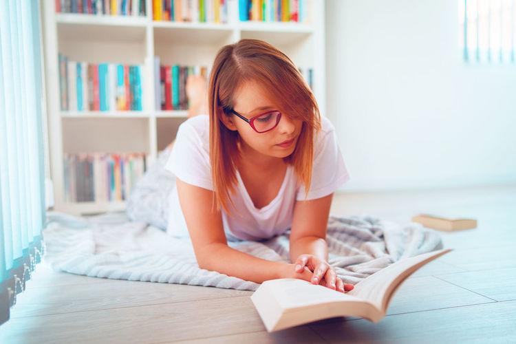 Beautiful woman wearing eyeglasses reading book lying on floor at home