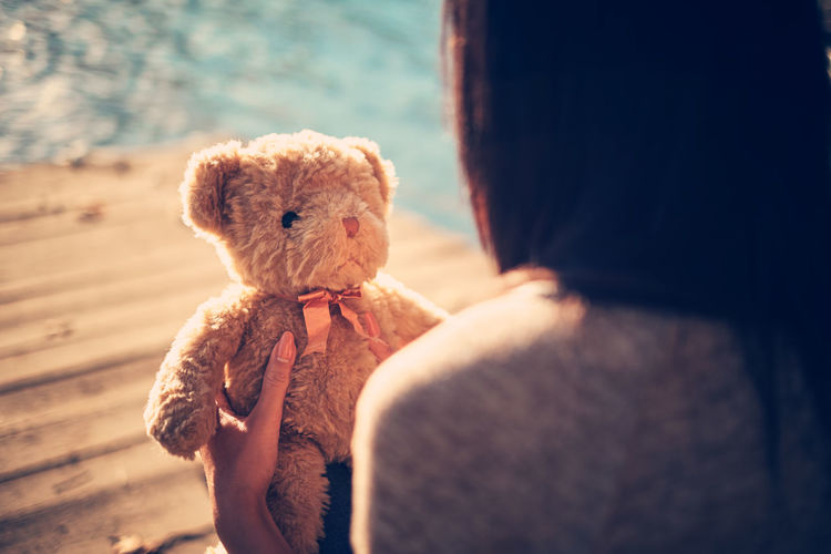 Close-up of woman holding teddy bear at lake
