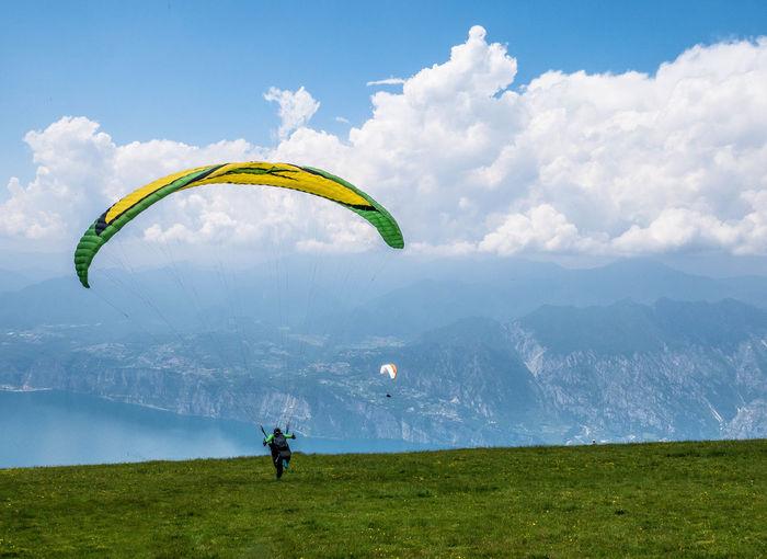 People paragliding on landscape