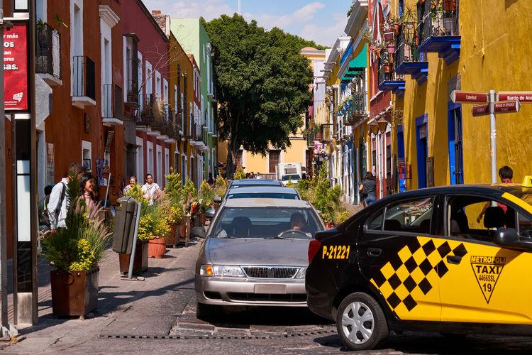 Car on street by buildings in city