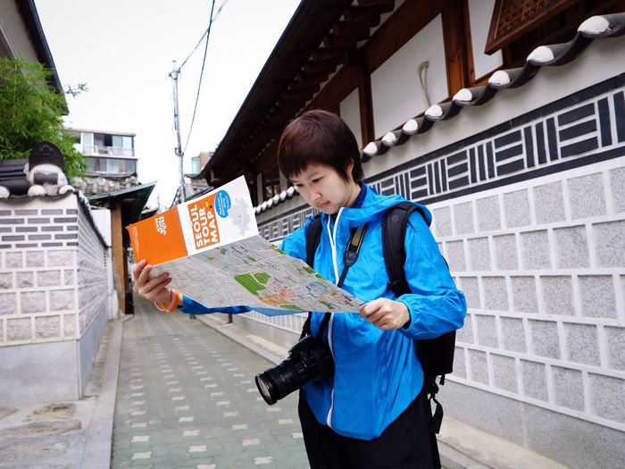 Full length of person reading map standing on city street in korea
