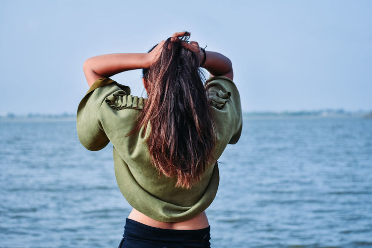 Midsection of woman standing by sea against sky and holding hair