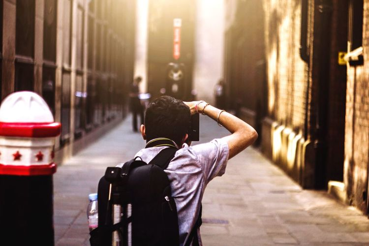 Young woman photographing in city