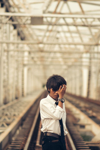 Young man standing on railroad track