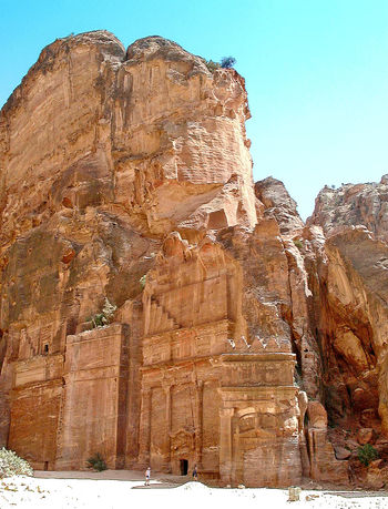 Petra (Arabic: البتراء, Al-Batrāʾ; Ancient Greek: Πέτρα), originally known as Raqmu (Nabataean Arabic: الرقيم), is a historical and archaeological city in southern Jordan. Petra lies on the slope of Jabal Al-Madbah in a basin among the mountains which form the eastern flank of Arabah valley that run from the Dead Sea to the Gulf of Aqaba. Established possibly as early as the 4th century BC as the capital city of the Nabataean Kingdom. The Nabataeans were nomadic Arabs who invested in Petra's proximity to the trade routes by establishing it as a major regional trading hub. In AD 106 Petra was annexed by the Roman empire. Rome's diversion of the caravan trade and some devastating earthquakes in subsequent centuries put the city into decline. Nabataean Kingdom Petra Jordan Ancient Architecture Arid Climate Beauty In Nature Clear Sky Cliff Day Geology Nature No People Outdoors Physical Geography Rock - Object Rock Formation Scenics Tranquil Scene The Traveler - 2018 EyeEm Awards