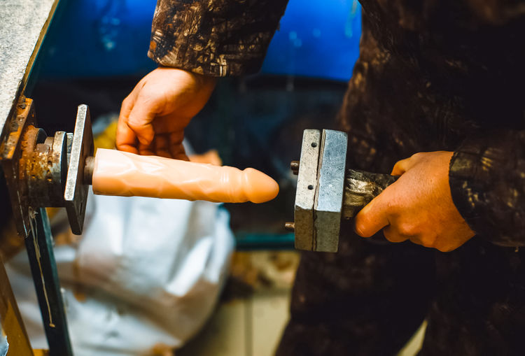 Cropped hands making dildo at workshop