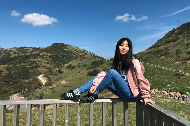 Portrait of smiling young woman sitting on railing against mountains