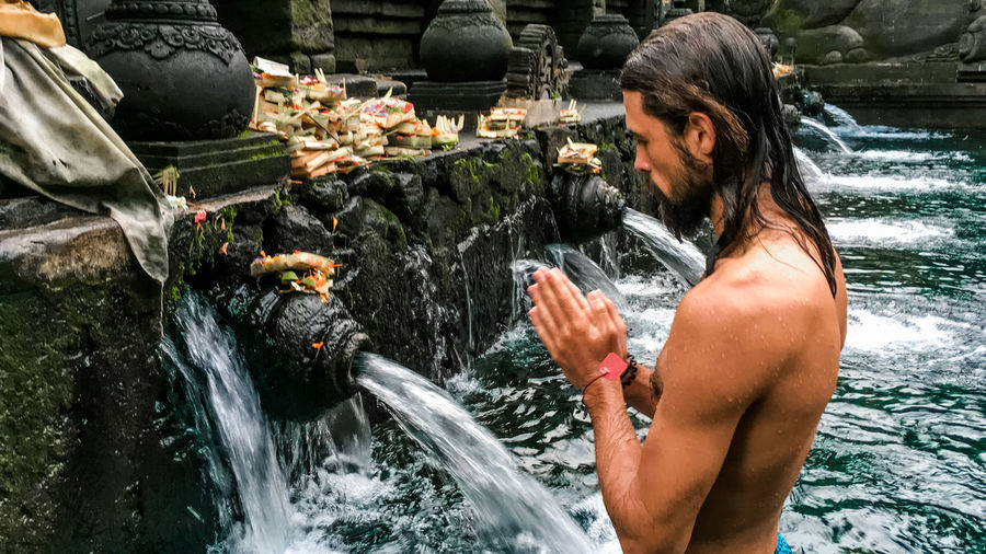 Shirtless man standing in water at temple