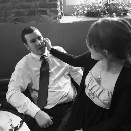 Man looking at woman sitting on lap in restaurant