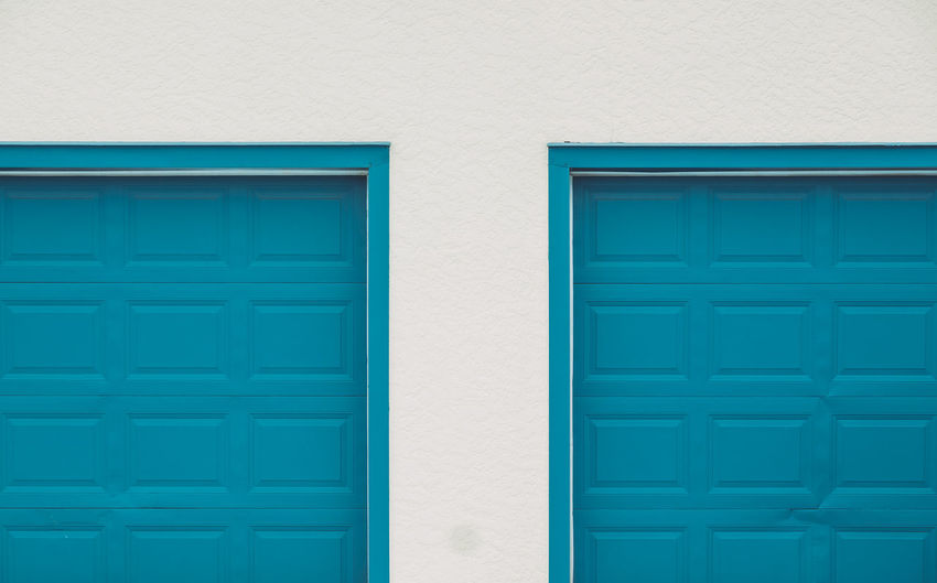 Turquoise wooden doors on white wall