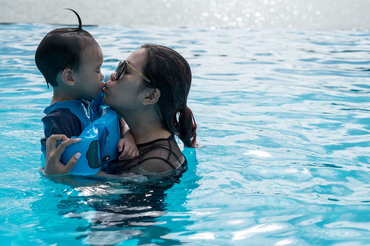 Mother Kissing Cute Son In Swimming Pool
