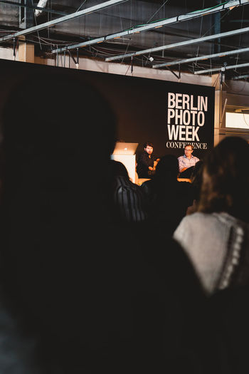 Berlin Photo Week 2018 Berlin Photo Week BPW18 EyeEem Real People Men Rear View Group Of People Text Women People Adult Communication Lifestyles Leisure Activity Architecture Night Built Structure Indoors  Illuminated Togetherness Sitting
